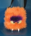 Orange monster bag with bushy eyebrows